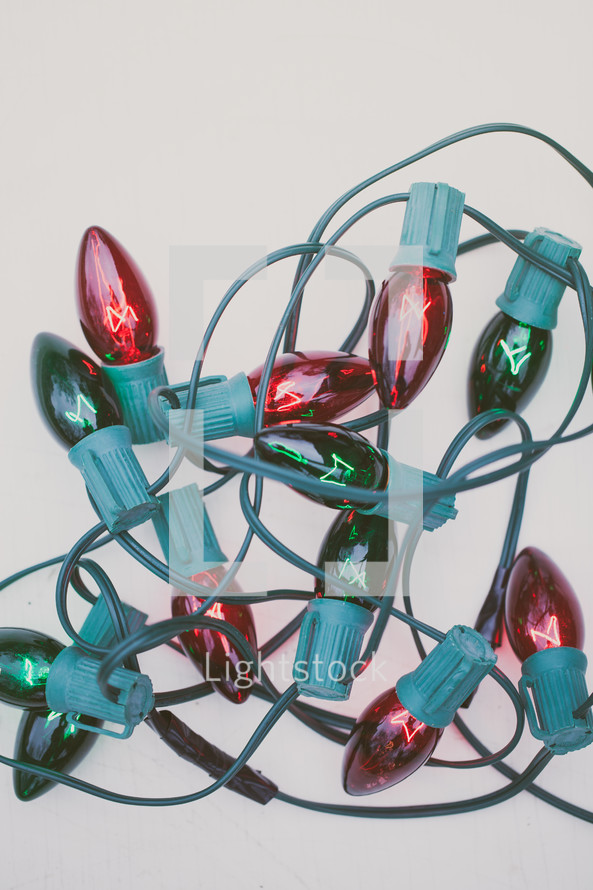 Red and green Christmas lights on a white background.