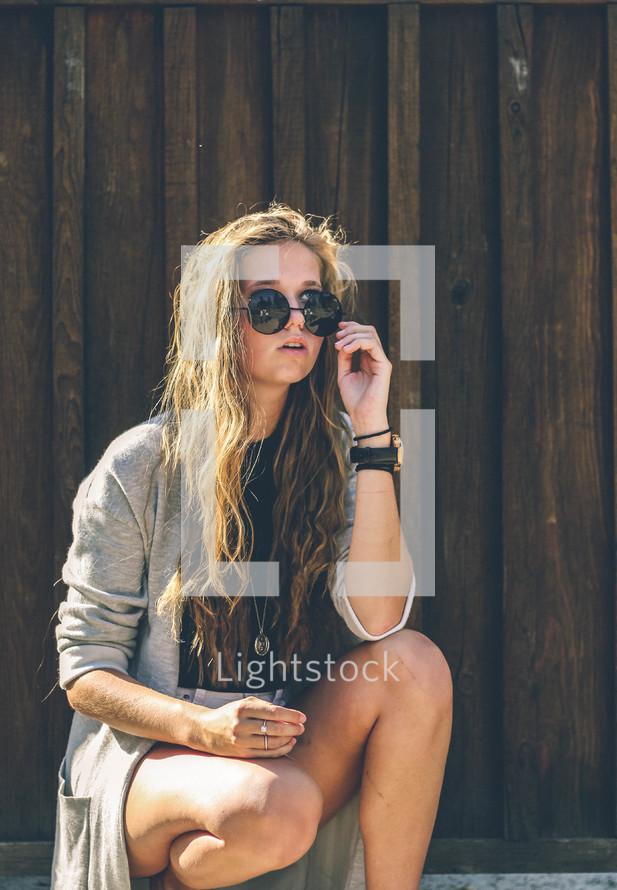 tree girl in sunglasses squatting