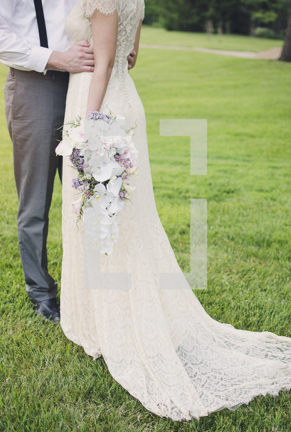 torso of a bride and groom standing in grass