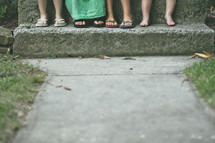 Kids' feet on a cement step.