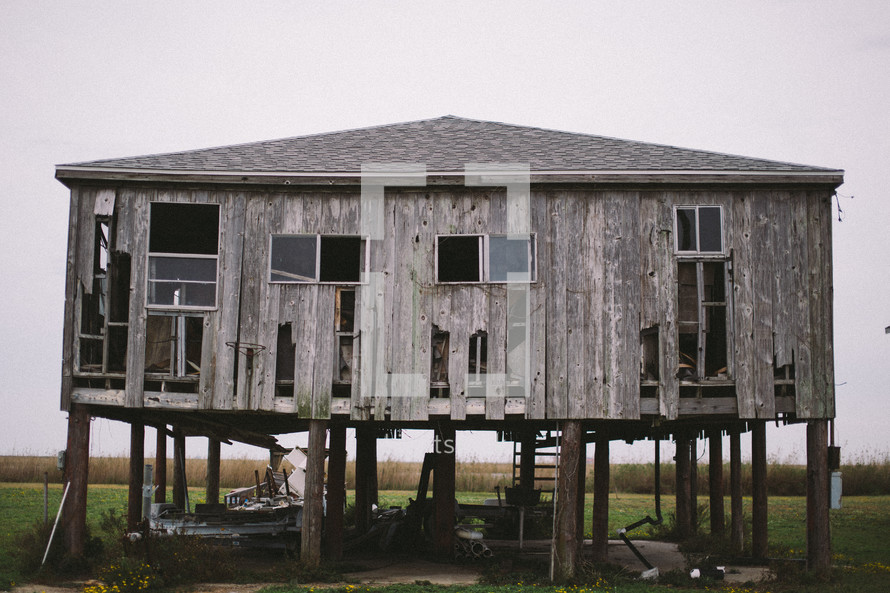 an abandoned house on stilts
