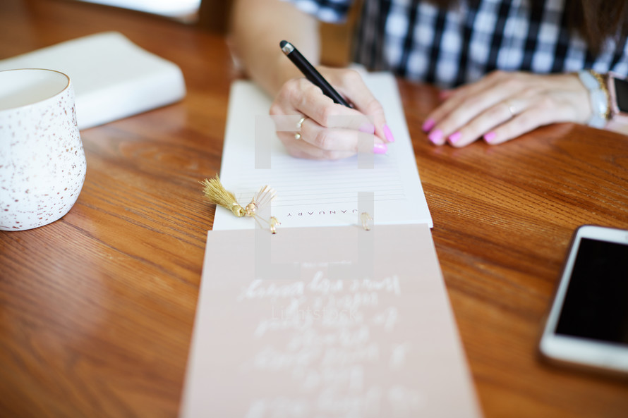 a woman sitting at a desk making a list