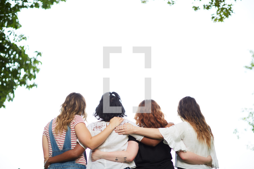 woman standing with arms around each other