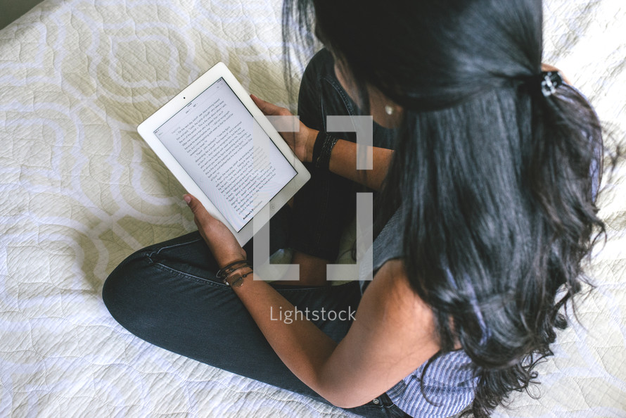 young woman reading a Bible on her bed