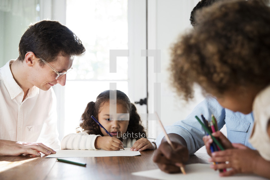 a family coloring together at the kitchen table.