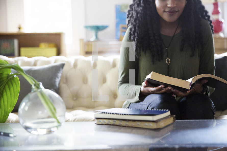 An African American woman reading a Bible in a living room