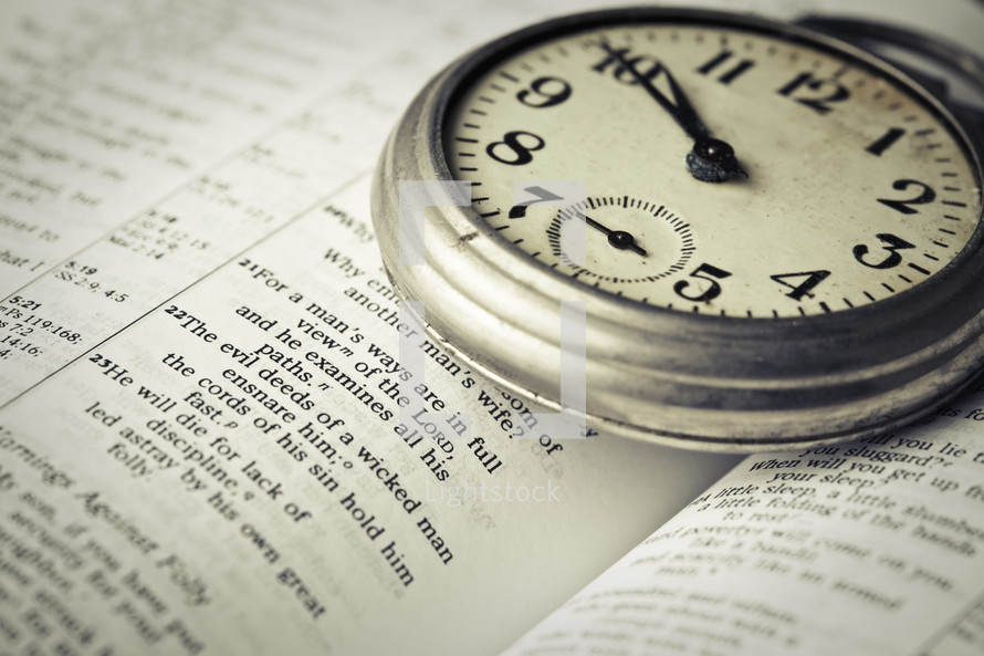 stopwatch on the pages of a Bible