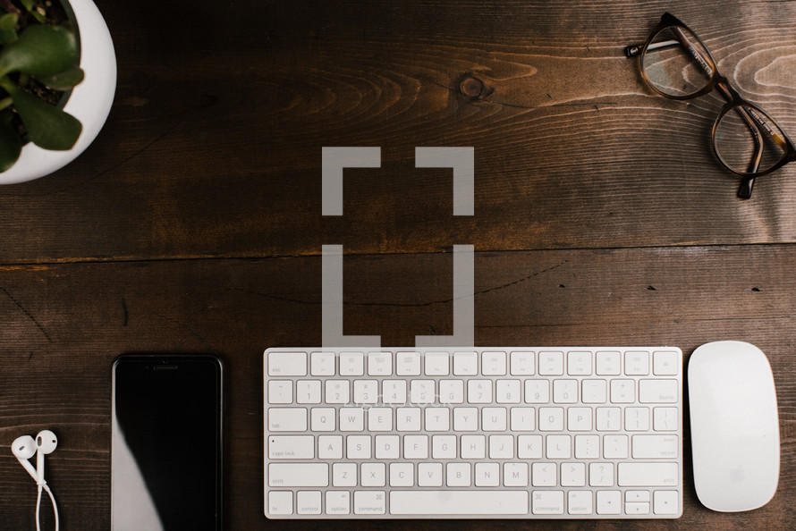 computer keyboard, computer mouse, house plant, and reading glasses on a wooden desk