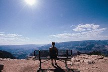 A young woman sits on a bench overlooking the Grand Canyon.
