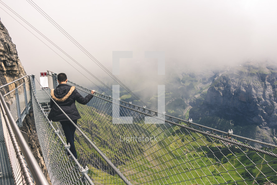 a man walking across a swinging bridge