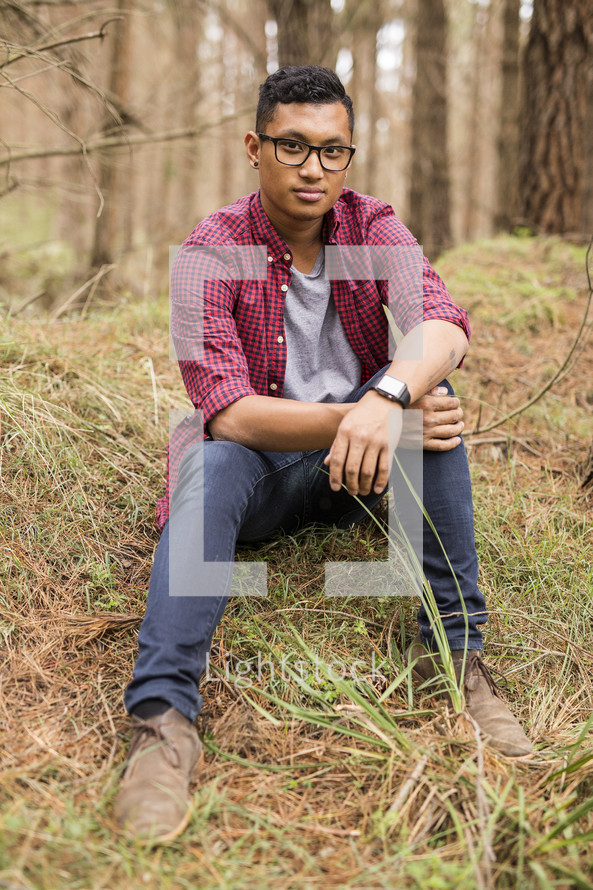 a portrait of a young man sitting on a grassy hill