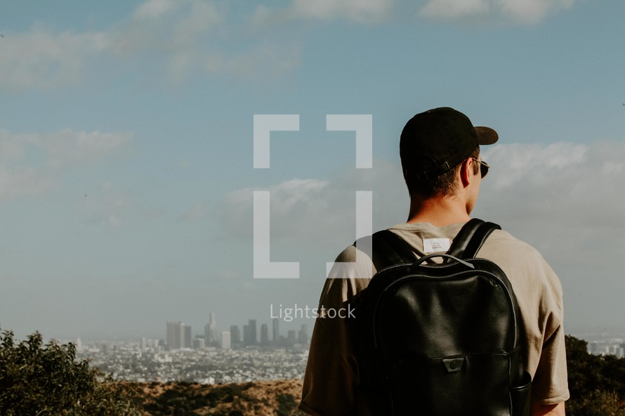 young man standing with a backpack looking out at a distant city