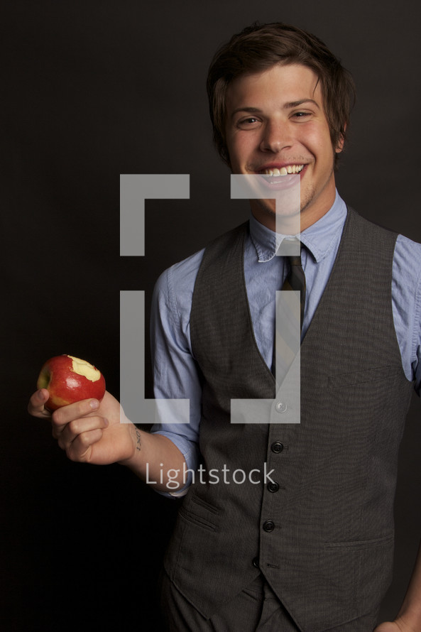 young man taking a bite out of an apple