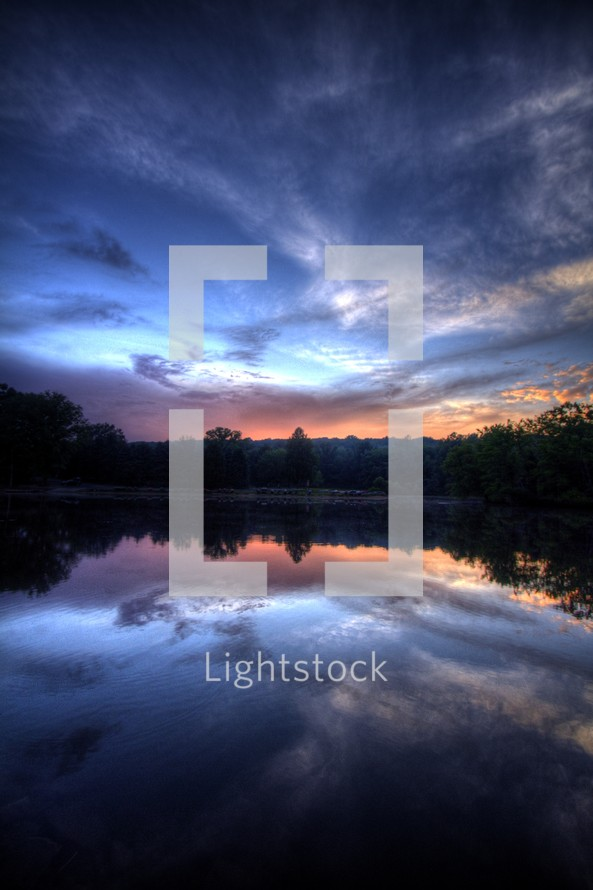 clouds reflecting in the water of a lake at sunset