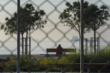 a man sitting on a bench looking out at the water