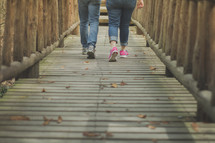Two women walking down a wooden bridge