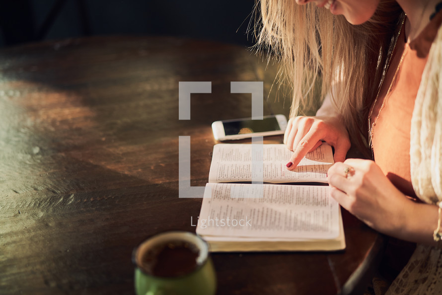 a woman reading a Bible over coffee