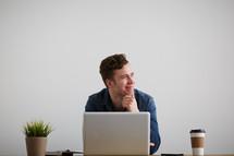 a man thinking sitting behind a computer