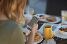 a woman checking her cellphone over breakfast