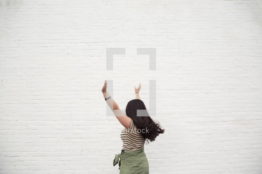a woman with open arms standing in front of a white wall