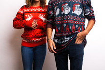 torsos of a couple in  ugly Christmas sweaters