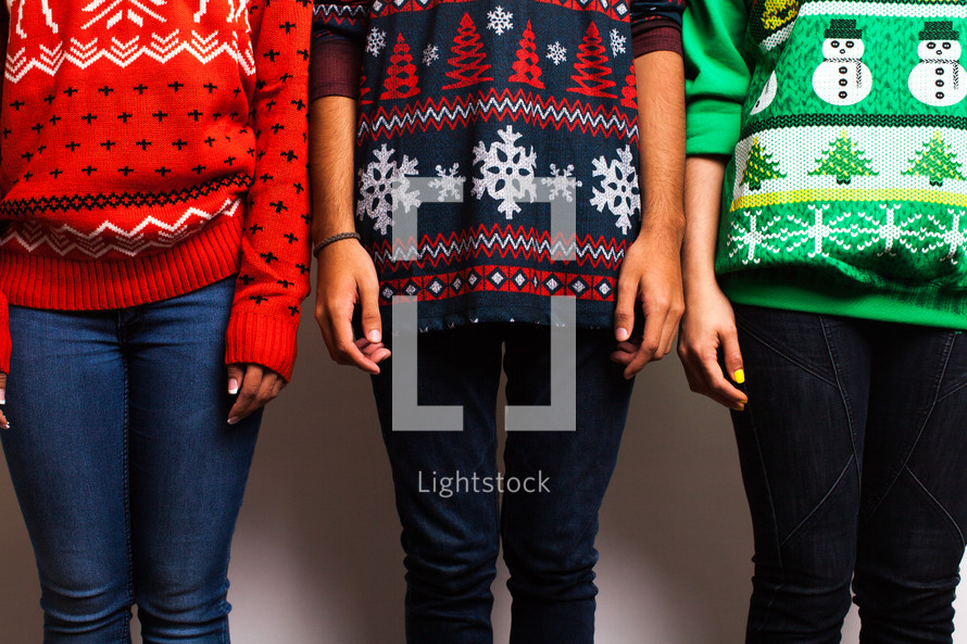 friends standing in ugly Christmas sweaters