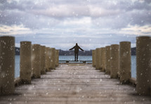 person standing at the end of a dock under falling snow