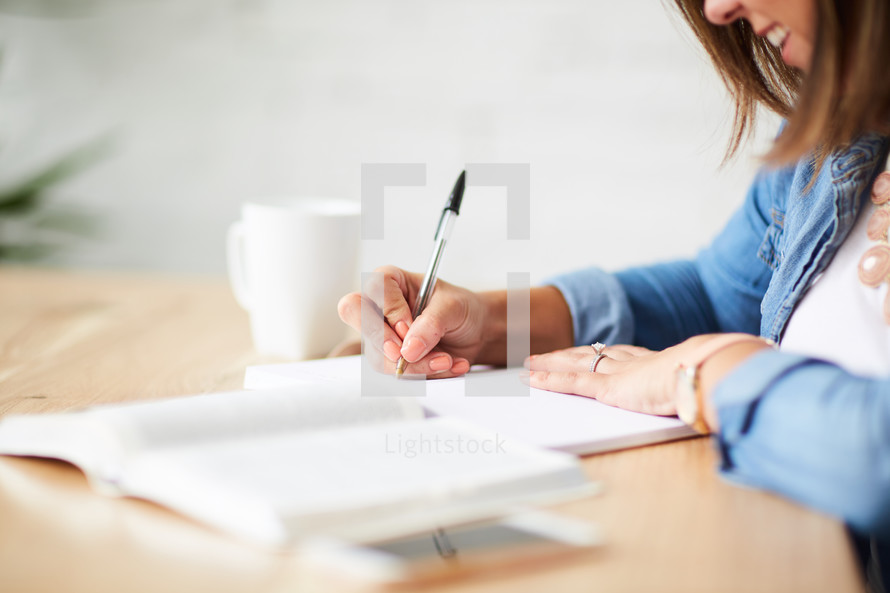 a woman writing in a journal and reading a Bible