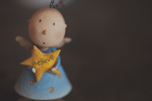 A Christmas doll with a star that says believe