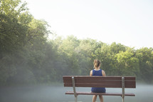 Woman sitting on a park bench .