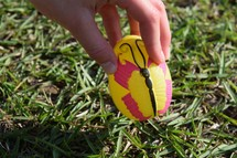 A child picking up an Easter egg at an Easter egg hunt
