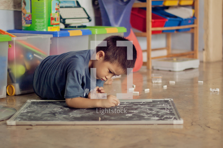 Asian boy child coloring on a chalkboard with chalk