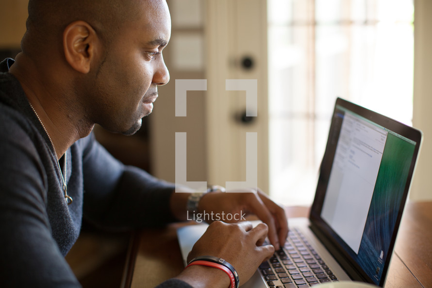African-American man typing on a laptop