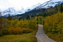 road leading to snow capped mountains