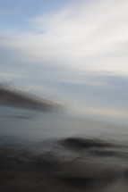 blurry image of ocean and shore