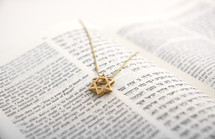 Open Hebrew/English Bible with a gold Star of David pendant on the page.