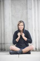 woman sitting wearing a hoodie