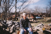 an elderly man sitting on a pile of cut logs