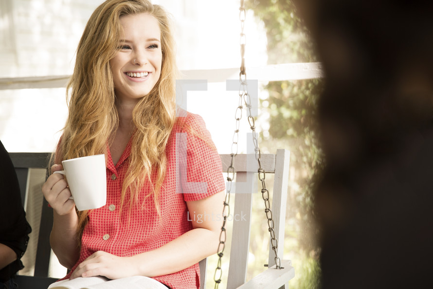 woman drinking a cup of coffee on a porch swing