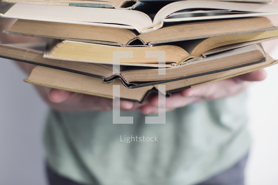 man holding open books stacked in a pile.