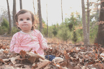 a toddler girl sitting in fall leaves