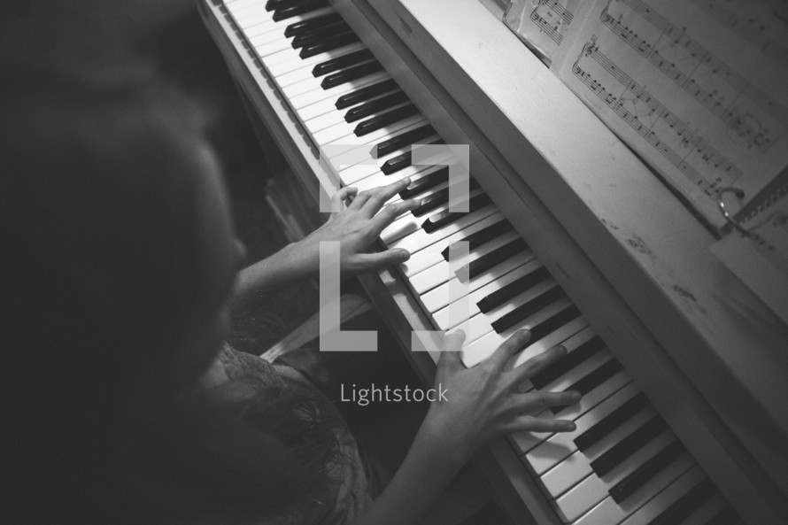 A girl playing a piano.