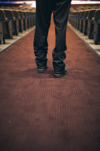 feet of a man standing in the aisle of a church