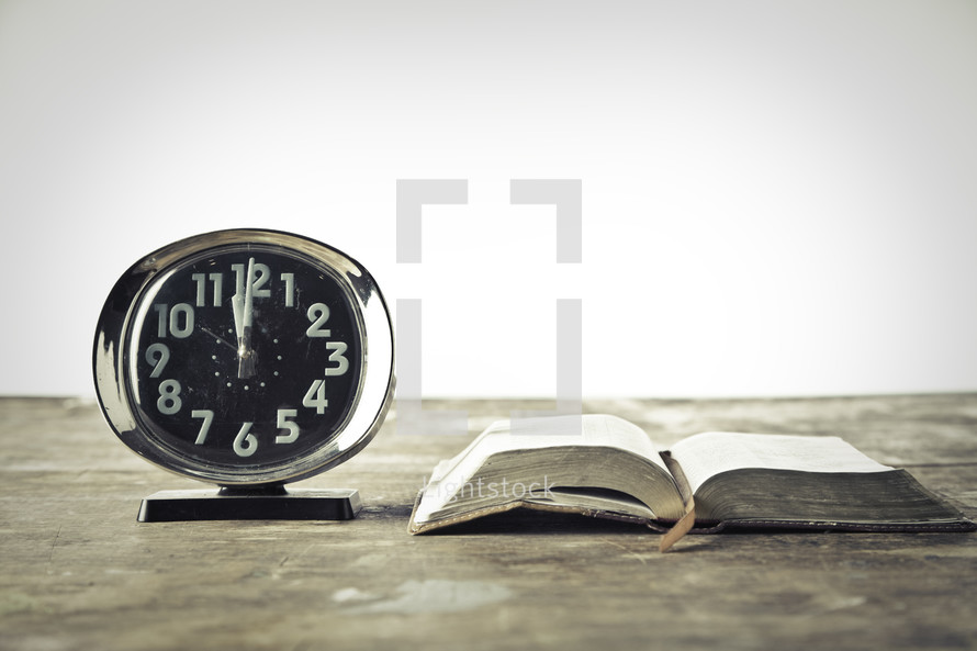alarm clock and an open Bible