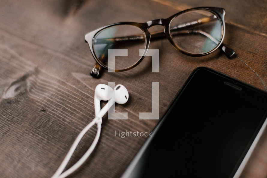 reading glasses and iPhone with earbuds
