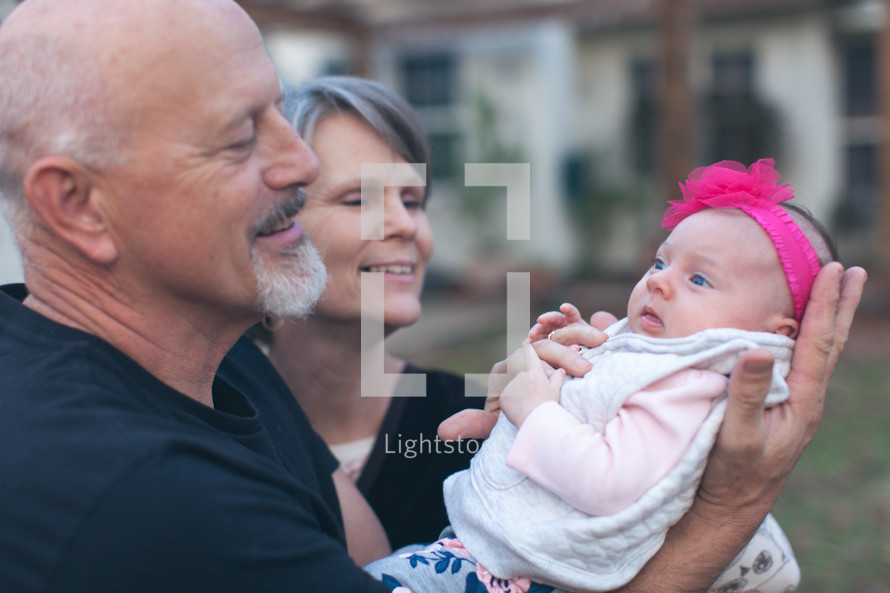 grandparents holding their infant granddaughter