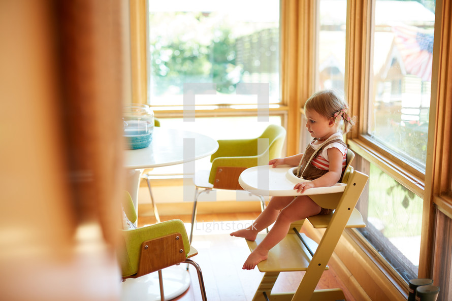a toddler sitting in a highchair