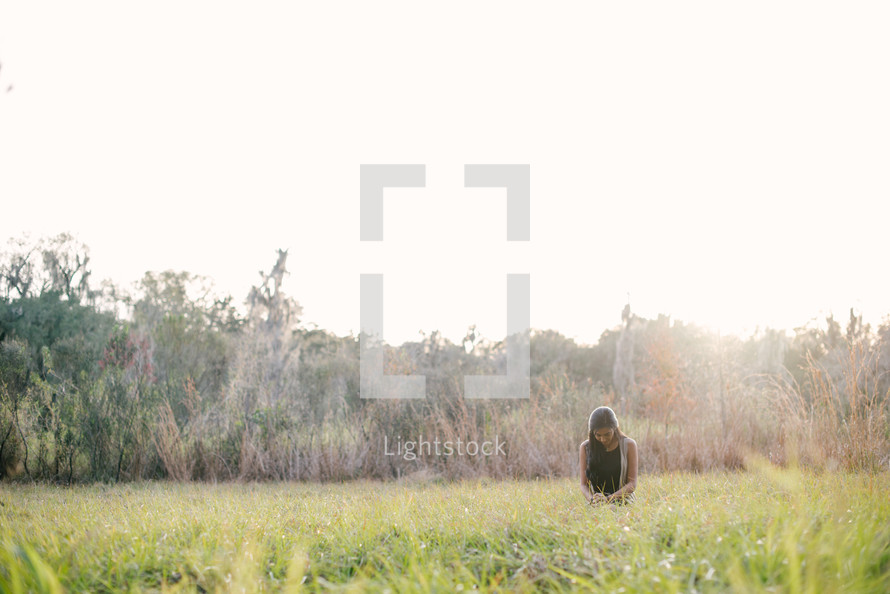 A young woman praying in a field of grass.