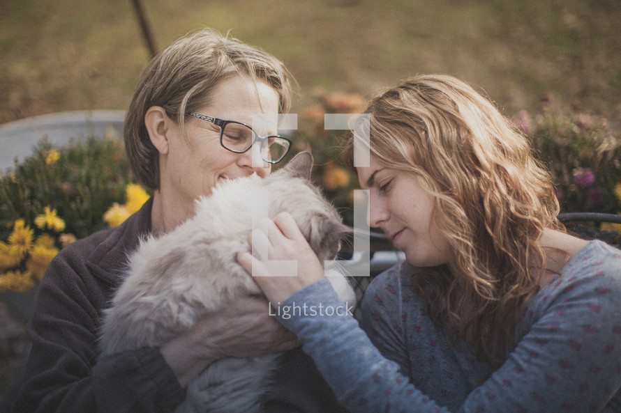 A mother and daughter petting their cat