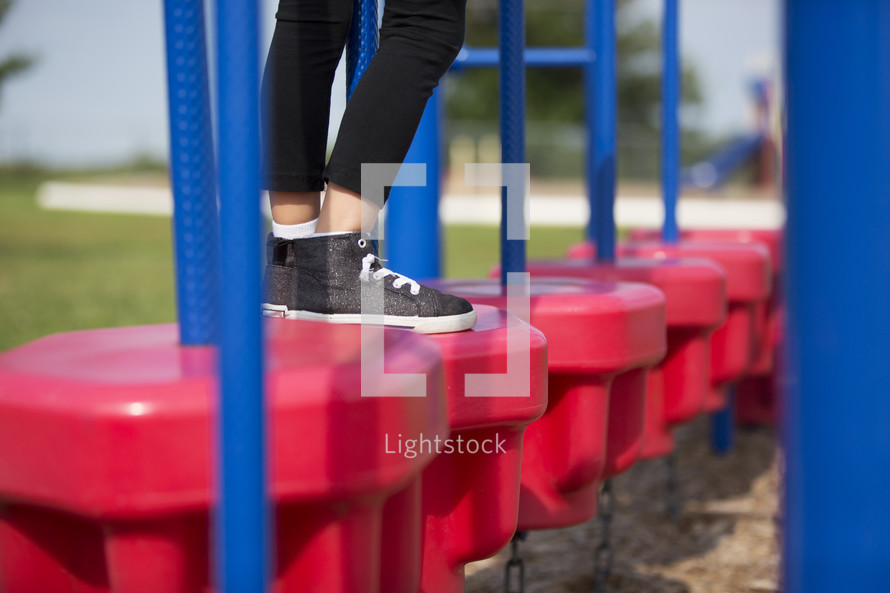 Legs and feet of a little girl playing on playground equipment.